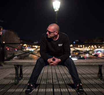 Photo de l'artiste Dj Duke assis sur un banc à Paris.